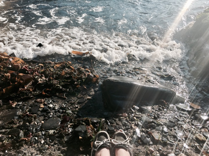 A pair of feet in Sperry boat shoes sitting on a rocky beach in Cornwall, England.