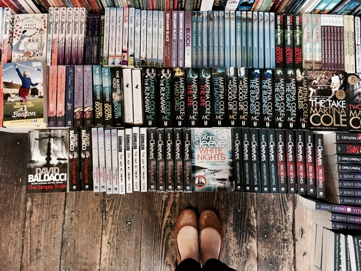 Feet on wooden floorboards surrounded by dozens of books.