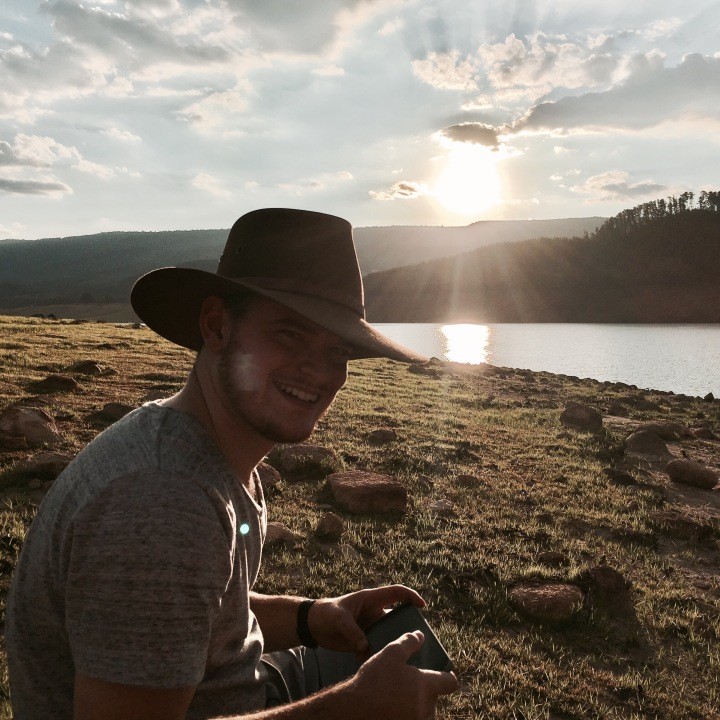 Man in Akubra hat watching sunset over a body of water.