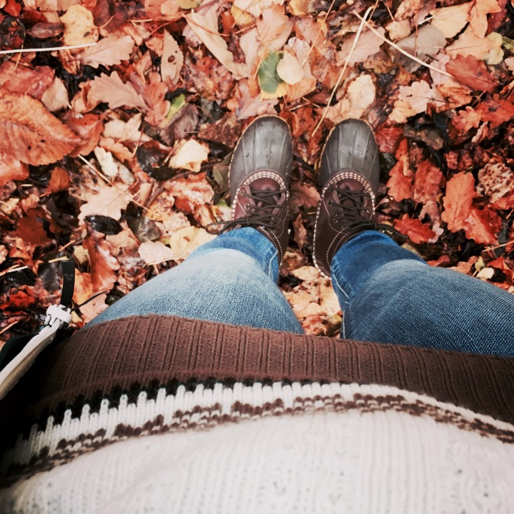 A woman in a pair of Bean Boots standing in a pile of autumn leaves.