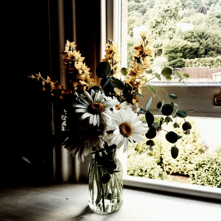 Bunch of yellow and white flowers sitting on a window sill.
