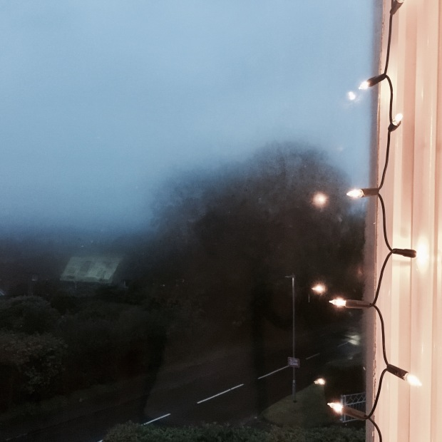 Fogged up window surrounded by fairy lights.