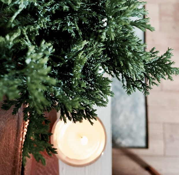 Conifer branches in a jar on a mantle, besides a lighted candle.