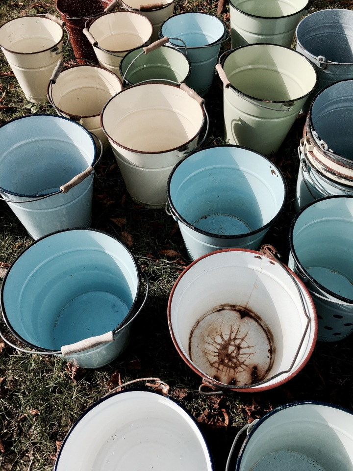 Enamel buckets for sale at a flea fair in Malvern, Worcestershire, England.