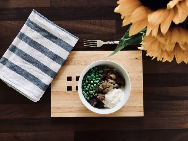 Beef stronganoff in a bowl, surrounded by a blue and white stripe napkin and a bunch of sunflowers.