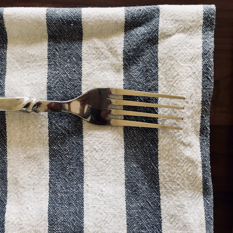 Fork sittting atop a blue and white striped linen napkin.
