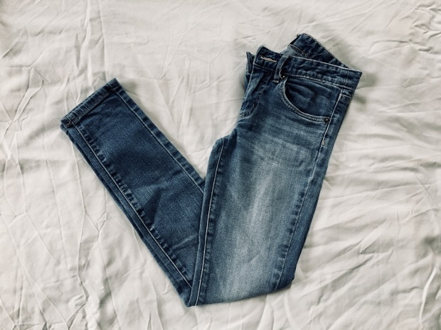 Flat lay of mid blue pair of jeans with fading across front.