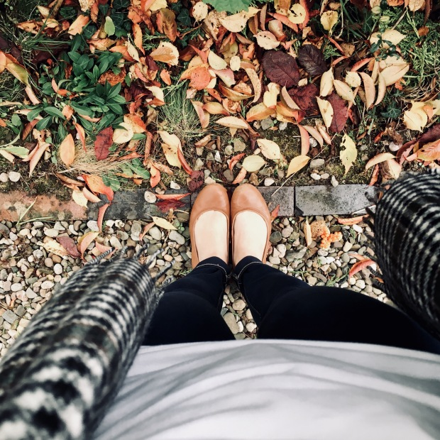 Looking down on a pair of legs wearing dark wash jeans and tan ballet flats surrounded by autumn leaves.