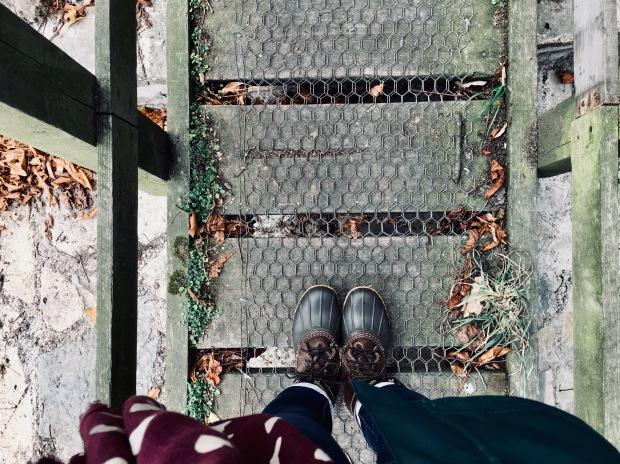 A pair of feet in Bean boots, walking across a wooden walkway in autumn.