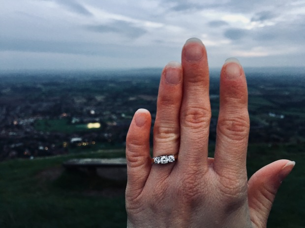 Hand wearing engagement ring.