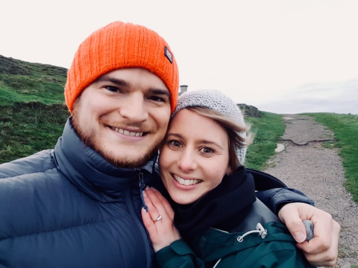 Newly engaged couple posing for a picture on the Malvern Hills in England.