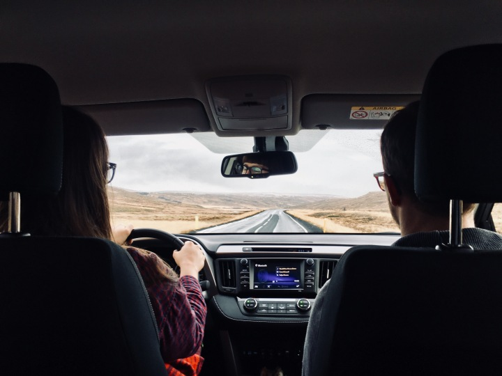 Man and woman in car driving in Iceland.