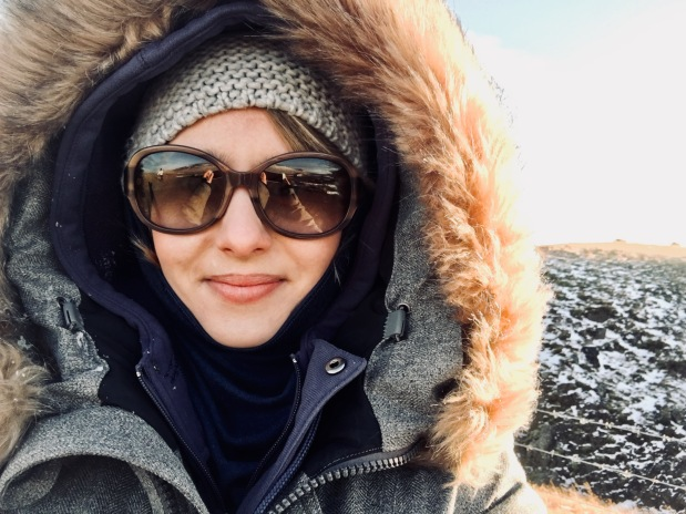 Woman rugged up in coat, wool hat and sunglasses in Iceland.