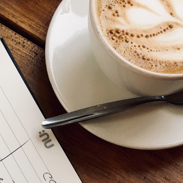 Notebook and coffee sitting on wooden table