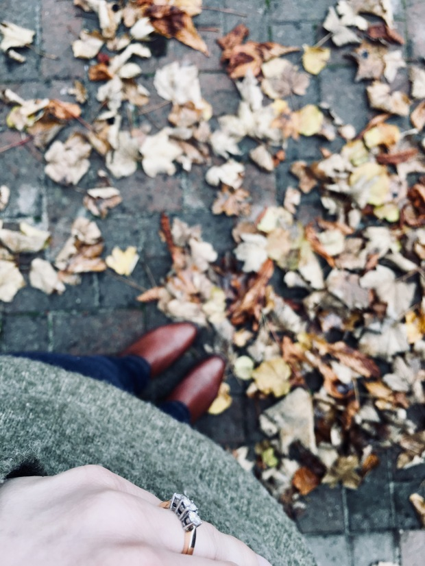 Engagement ring on woman wearing green jumper, jeans and boots surrounded by autumnal leaves
