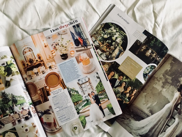 Wedding magazines laying open on an ivory sheet