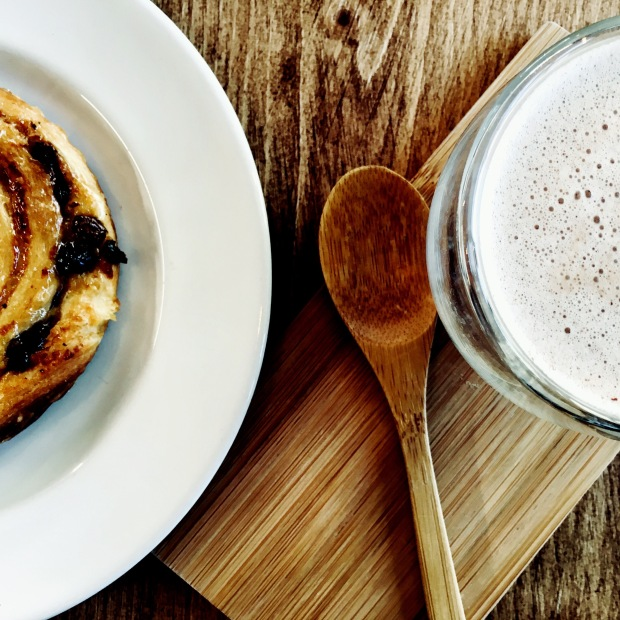 Pastry and hot chocolate sitting on wooden table.