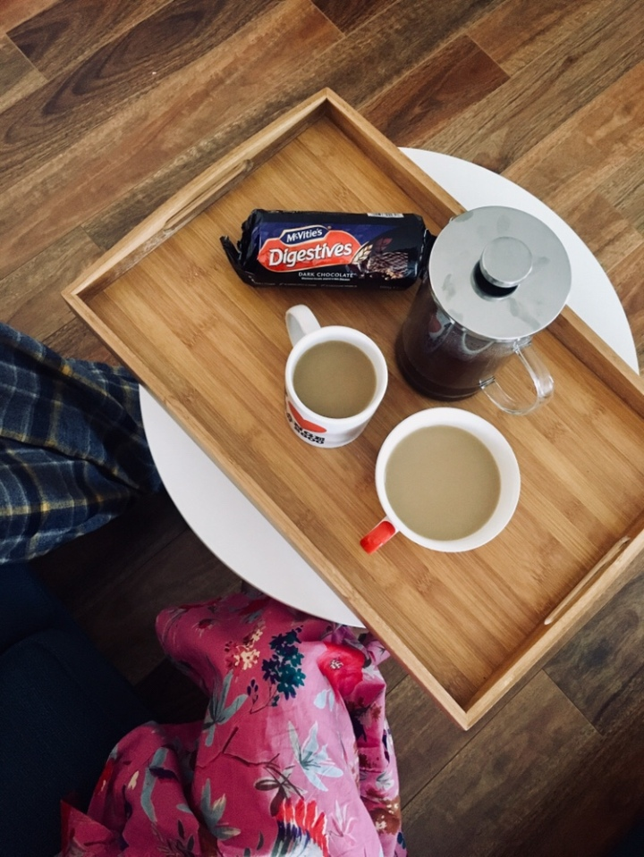Couple in pyjamas drinking coffee and eating chocolate Digestive biscuits.