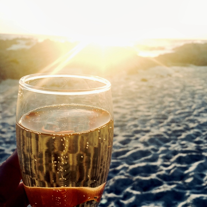 Glass of champagne on the beach at sunset.