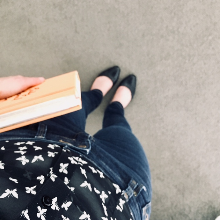Woman holding book wearing black flats, jeans and black shirt.