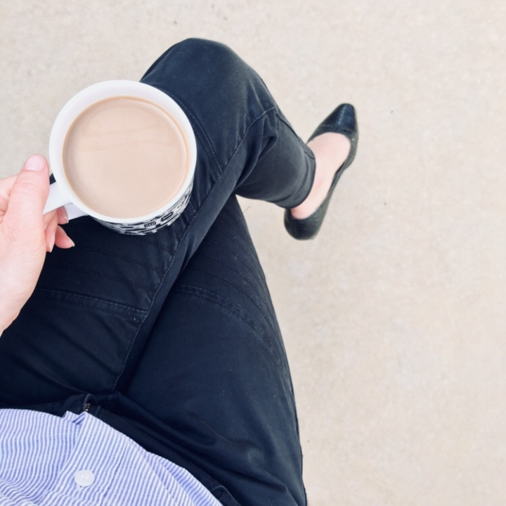 Woman holding cup of coffee wearing black flats, jeans and blue stripe shirt.