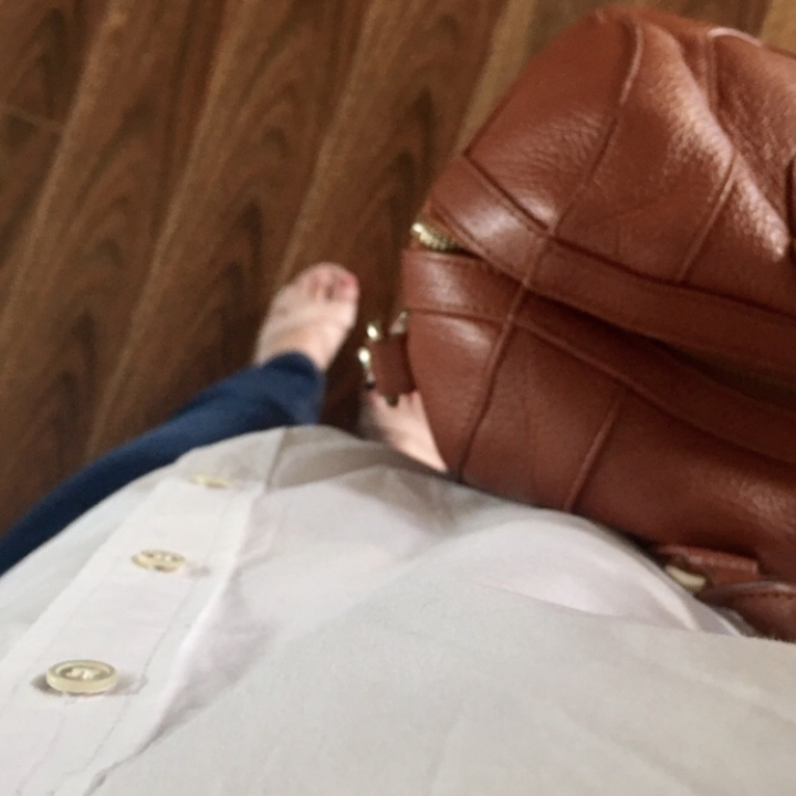 Woman wearing nude sandals, jeans and white shirt, holding a tan leather bag.