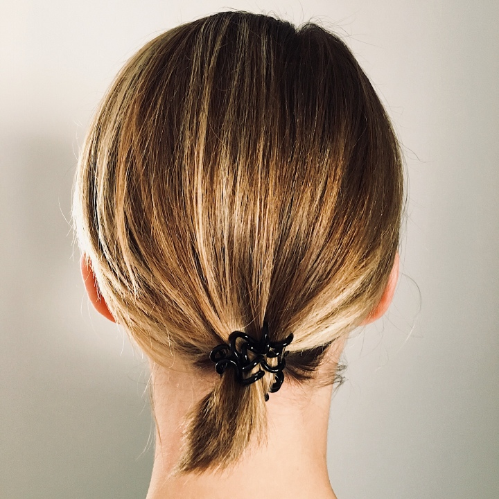 Back of a woman's head, where hair is tied up into a small, low pony tail.
