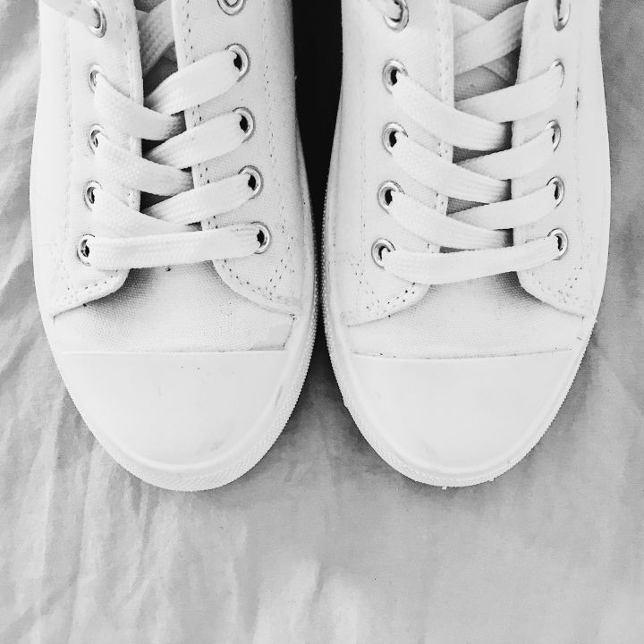 Pair of white sneakers on grey background.