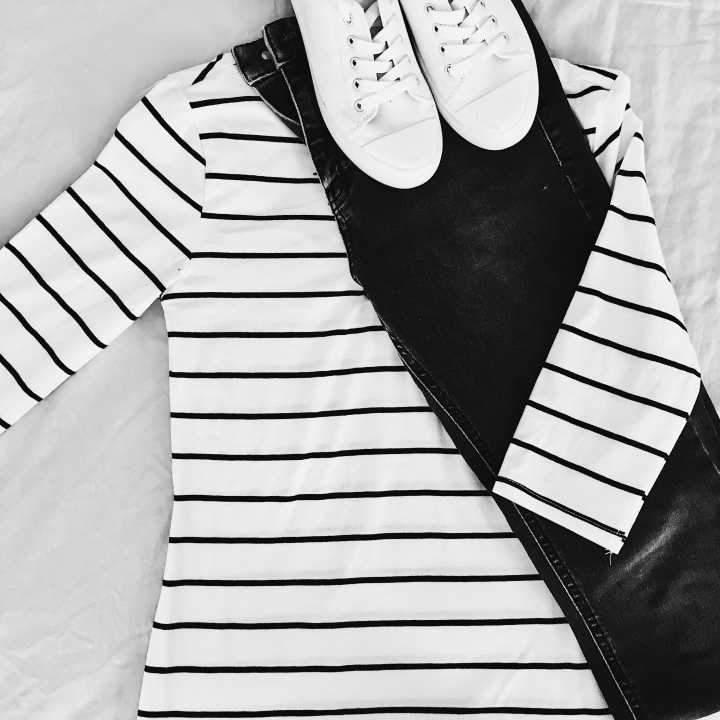Flatlay of black jeans, black and white stripe t-shirt and white sneakers.