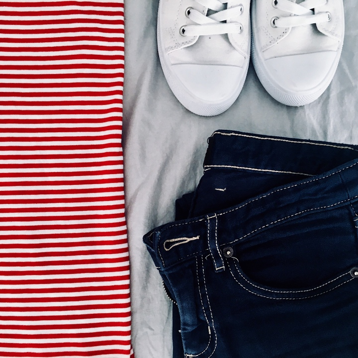 Flat lay of dark blue jeans, red and white stripe shirt and white sneakers.