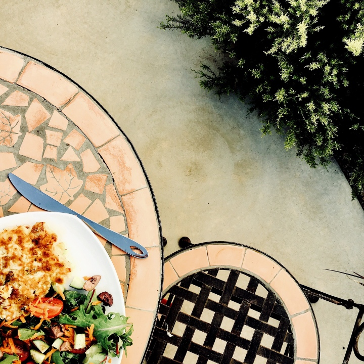 Salad and fritters sitting on an outside table.
