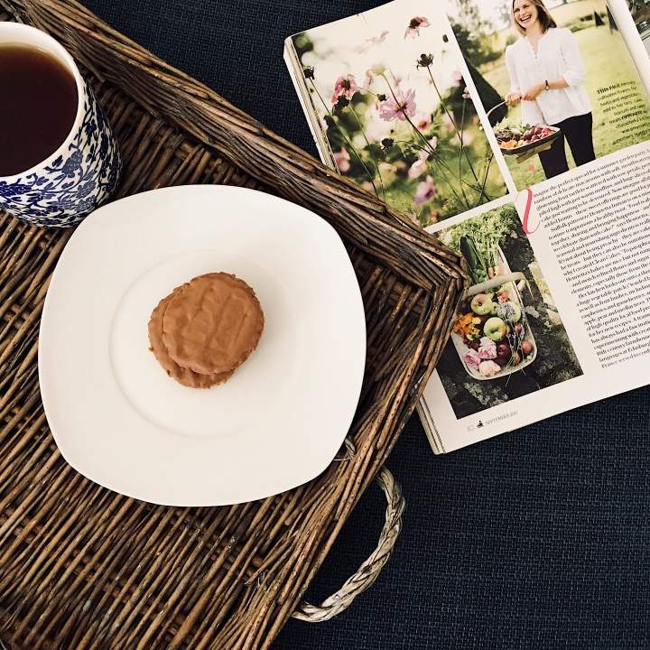Magazine open beside cup of tea and plate of biscuits.