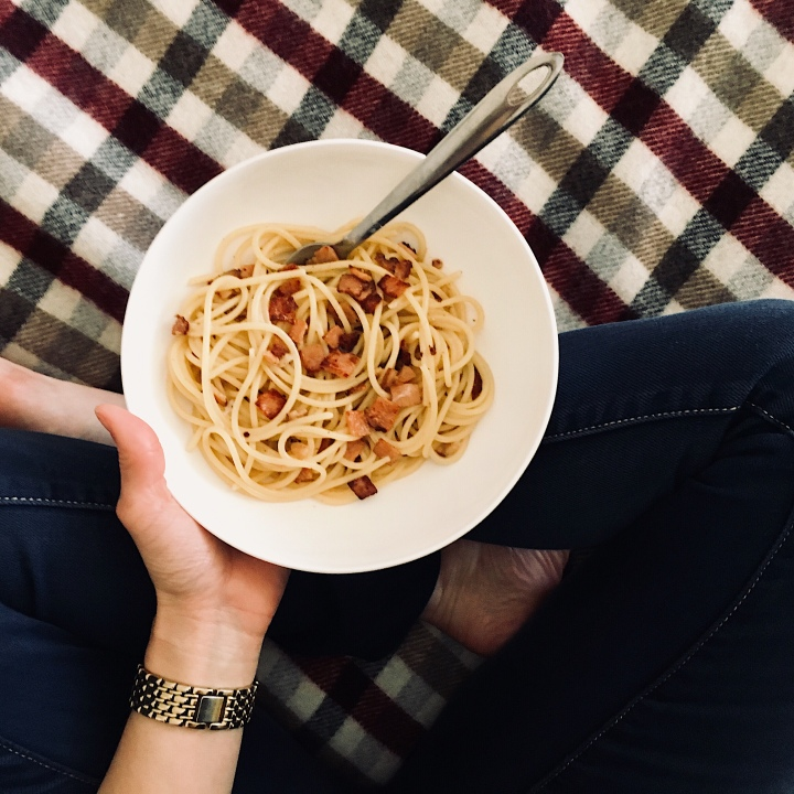 Hand holding bowl of pasta on check wool blanket