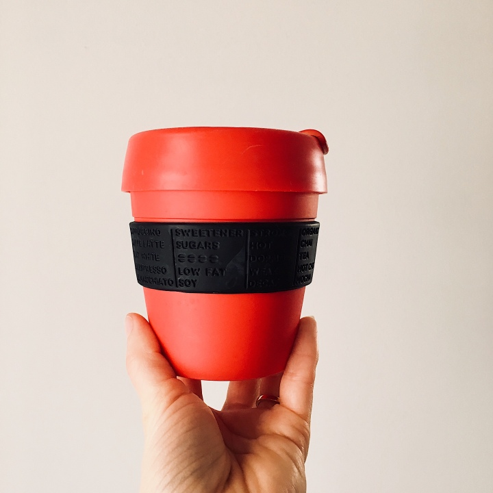 Hand holding a red reusable coffee cup.