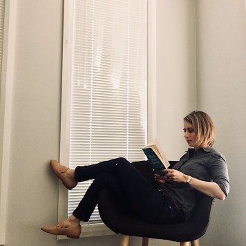 Woman reading wearing dark chambray shirt, dark blue jeans and nude loafers.