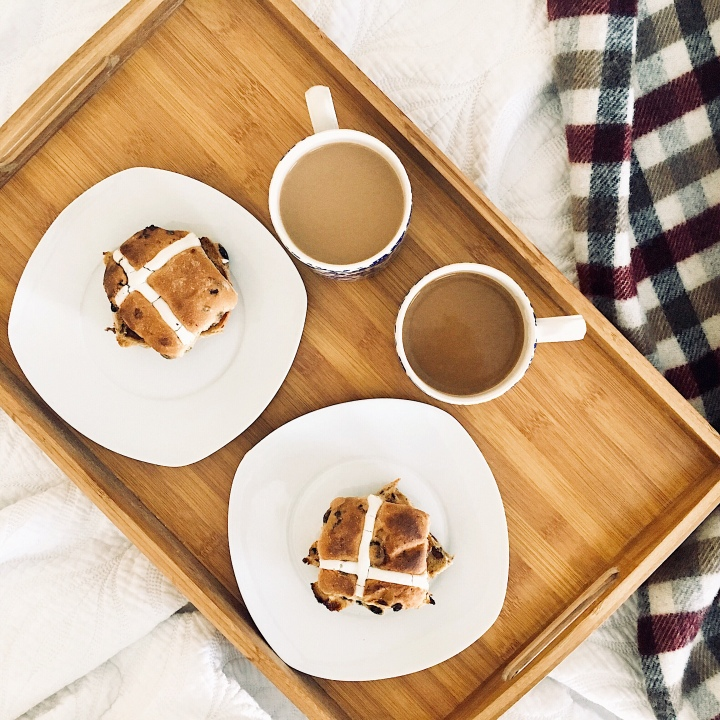 Flat lay of a tray sitting on an unmade bed with two cups of coffee and two toasted hot cross buns.