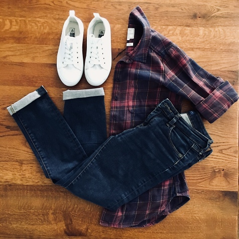 Dark blue jeans, navy and burgundy check shirt and white sneakers.