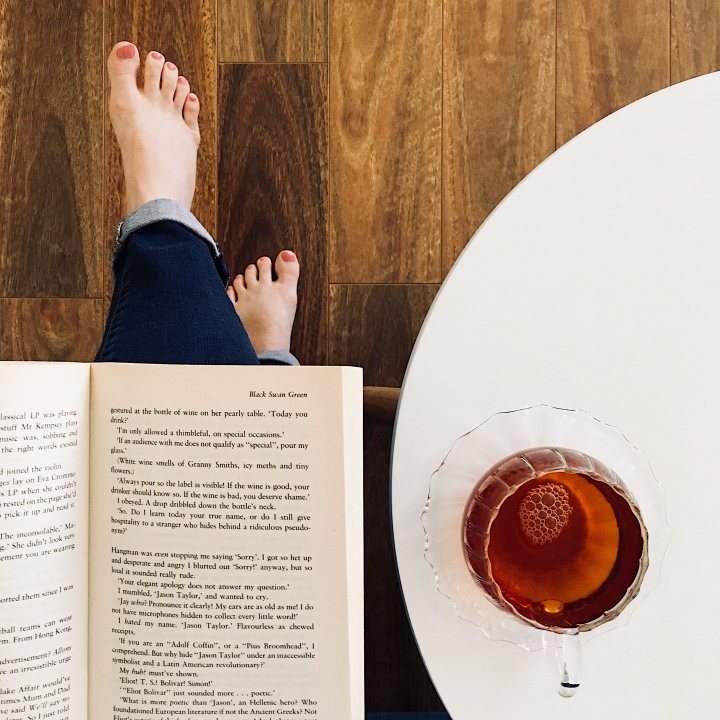 A barefoot woman in jeans drinking tea and reading a book.