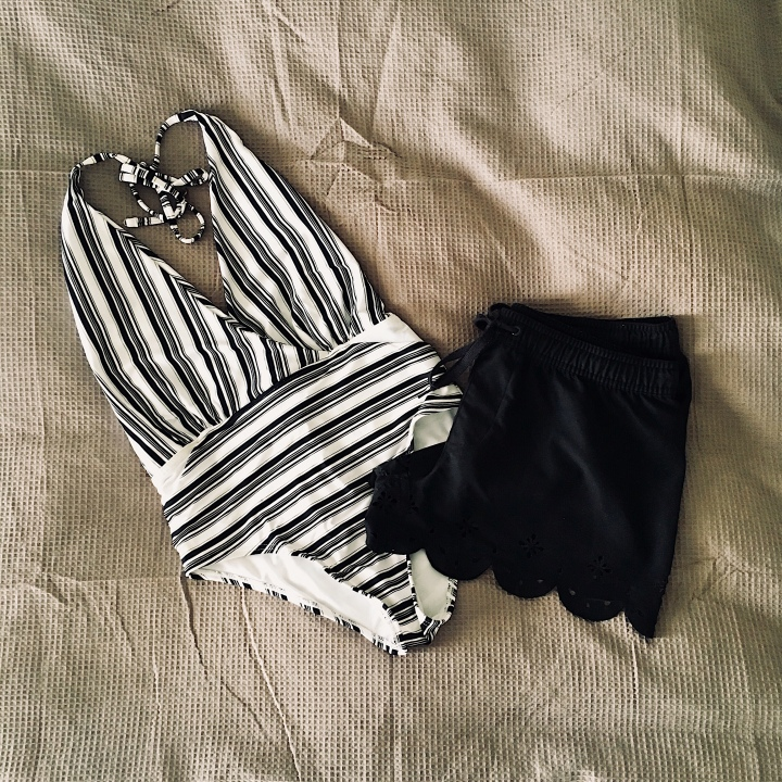 Black and white striped one piece swimsuit and black board shorts.