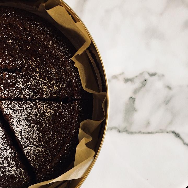 Nigella Lawson's chocolate olive oil cake sitting in a cake tin.