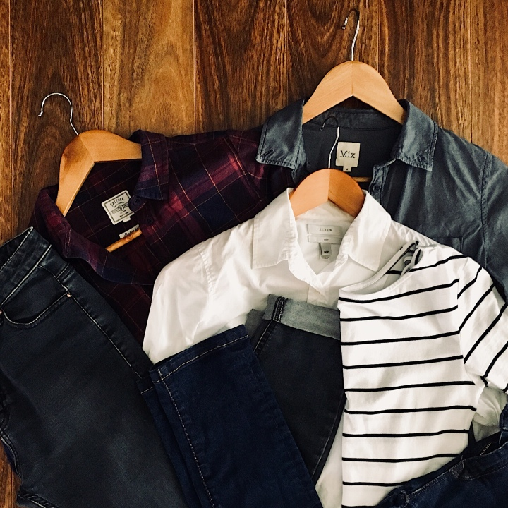 Flat lay of shirts, jeans and a stripe t-shirt.