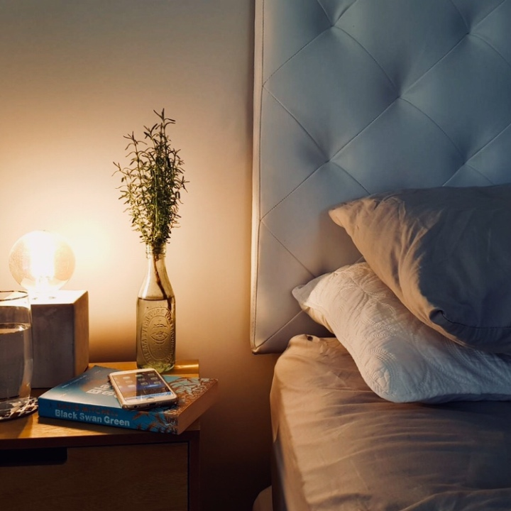 Bed and bedside table with vase, lamp, glass, book and phone on it.