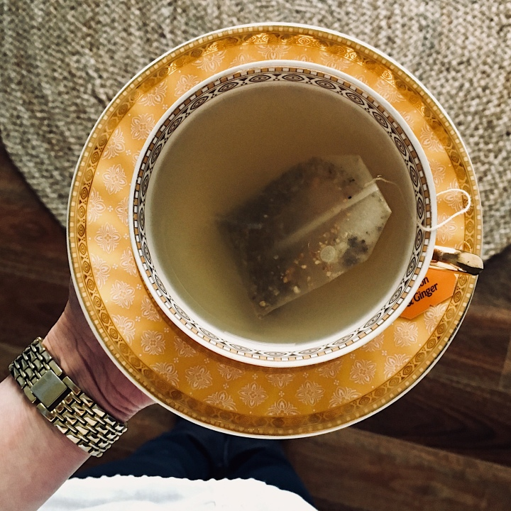 Hand holding cup of tea.