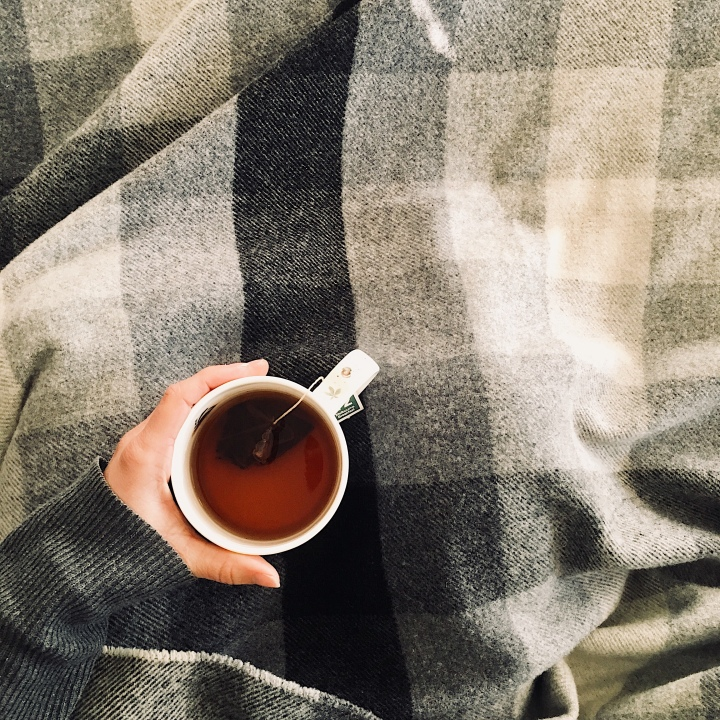 Woman sitting under a black and white wool check blanket holding a cup of tea.