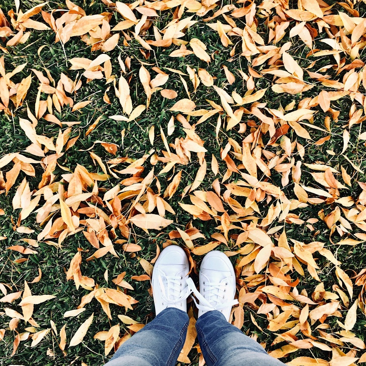 Woman wearing white sneakers and jeans standing in a pile of yellow leaves.