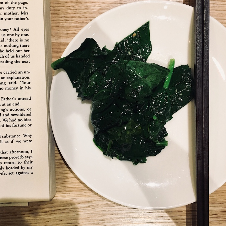 Book, plate of sauteed spinach and chopsticks.