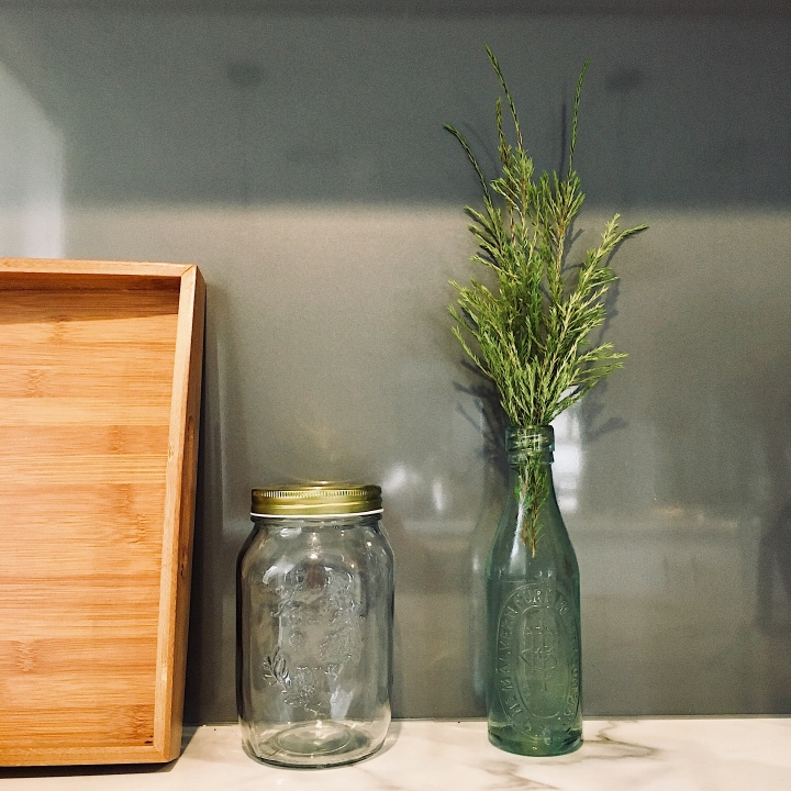 Greenery displayed in a bottle on a kitchen bench top.