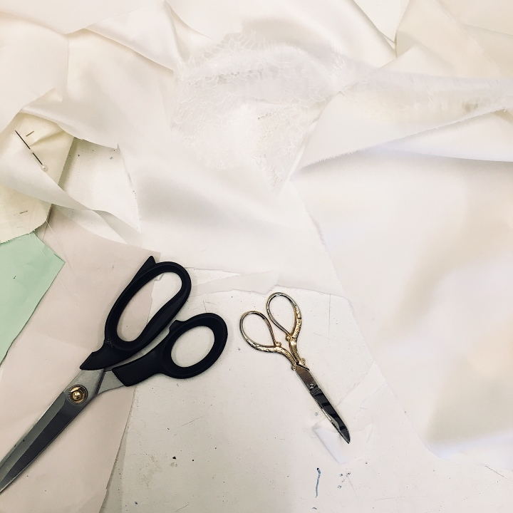 Material, scissors and a pattern on a sewing table.