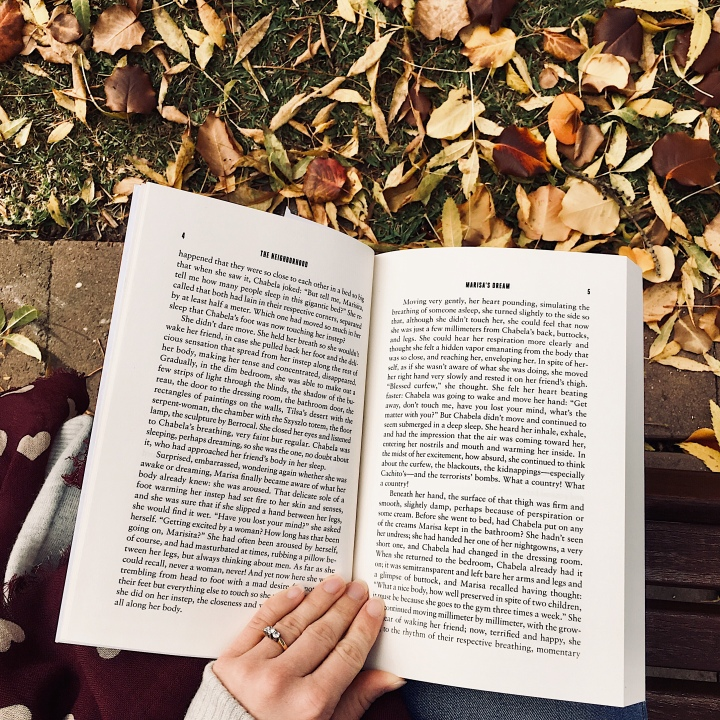 Woman reading on park bench surrounded by autumnal leaves.