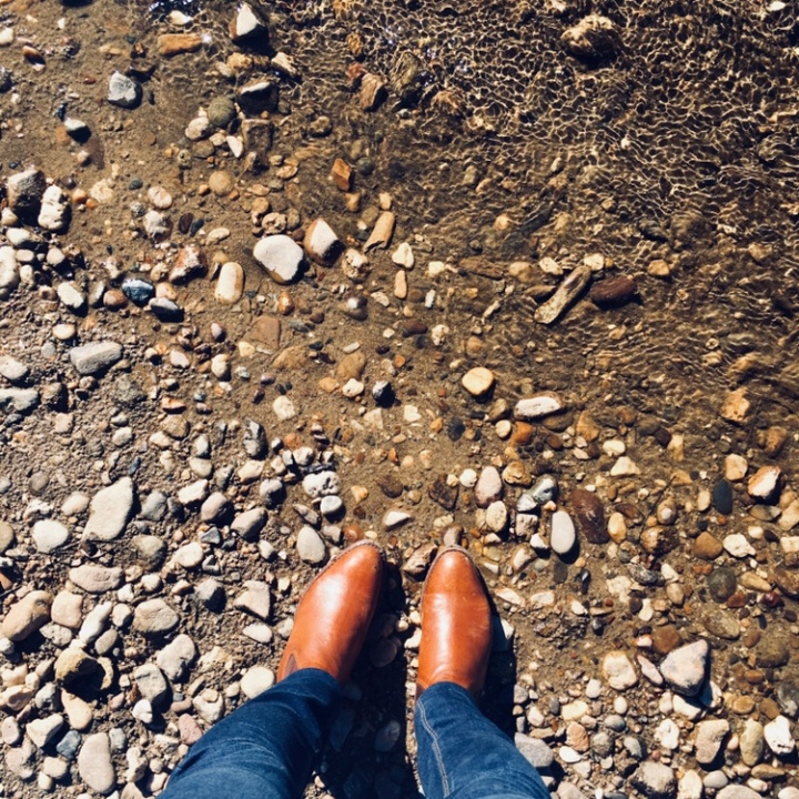 Looking down at a pair of RM Williams boots standing on the rocky shore of the Murrumbidgee River at Oura, New South Wales, Australia.